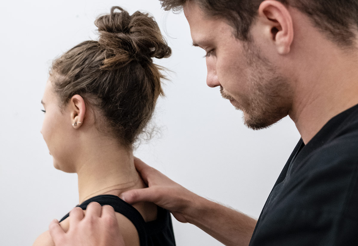 chiropractor checking the cervical spine of female patient suffering from neck pain