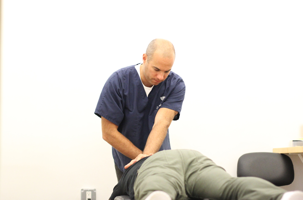 Dr Shoshany performing a chiropractic adjustment on a patient's spine. Adjusting the sacroiliac joint can often relive back and spinal pain and discomfort. Greenwich village chiropractor NYC