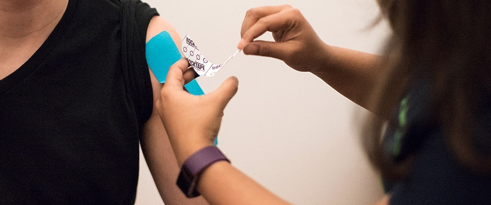 kinesio taping a patient suffering from muscular pain from a workout injury