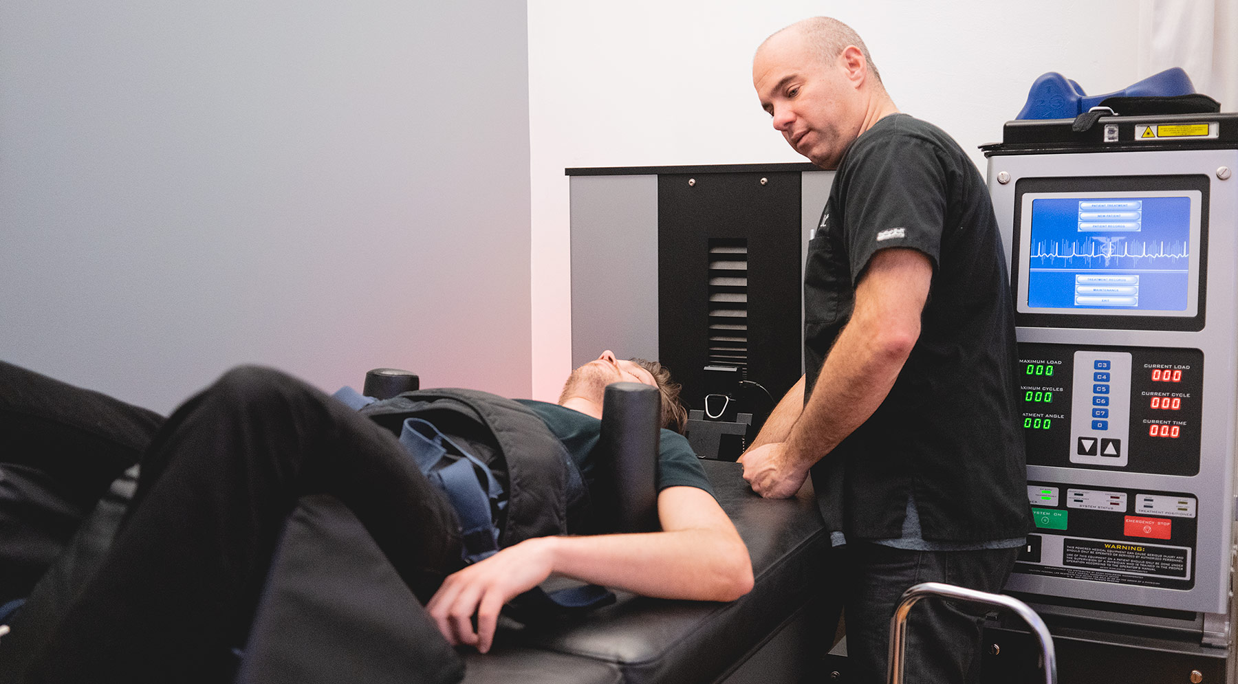 chiropractor treating patient with herniated discs using the drx9000 device